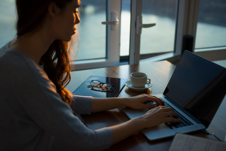 אישה כותבת על מחשב נייד באור של סוף היום הנכנס מהחלון