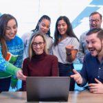 טרנד בתקשורת: עובדים במשרד סביב מחשב נייד